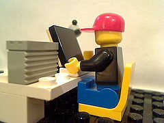Lego man sitting at computer